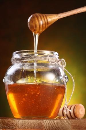 jar: Dulce miel a raudales de drizzler en el pote. Olla está en la mesa de madera.