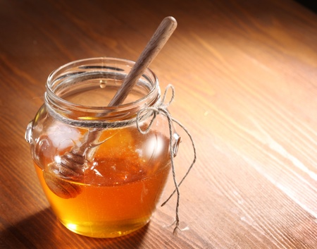 Pot of honey and wooden in it.  Object is on wooden table. photo