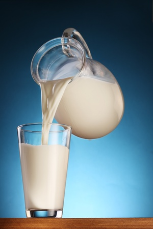 jugs: Milk pouring from jar into glass on a blue background. Stock Photo