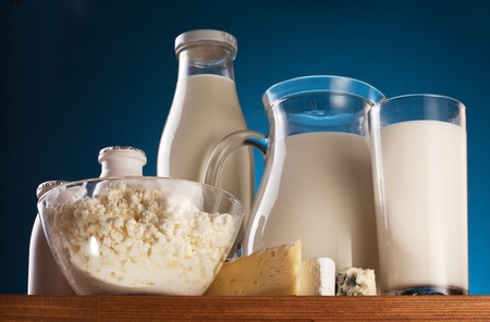 Different milk products: cheese, cream, milk, yoghurt. On a blue background. Stock Photo - 8296169