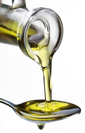 teaspoon: Olive oil flowing from carafe into the spoon isolated on a white.