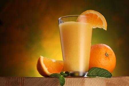 jus orange glazen: Stilleven: sinaasappelen en glas sap op een houten tafel.