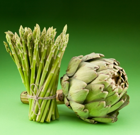Artichoke and asparagus on a green background photo