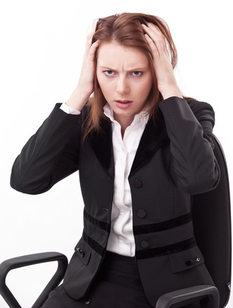 Depressed young woman sitting on a chair, clutches her head. photo
