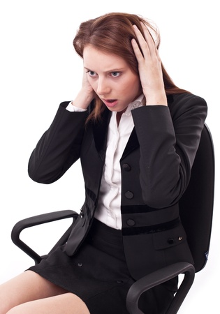 clutches: Depressed young woman sitting on a chair, clutches her head.