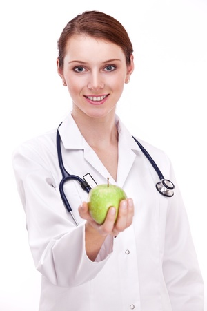 Smiling doctor with apple in her hand, likes she is giving it to you. photo