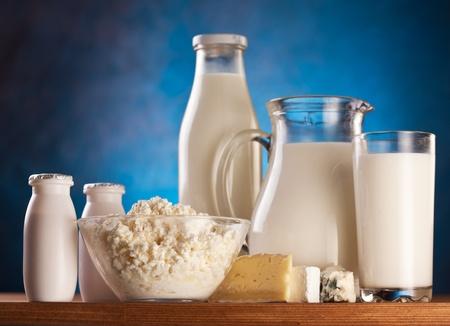 leche y derivados: Productos l�cteos diferentes: crema, leche, yogur y queso cottage.  Sobre un fondo azul.