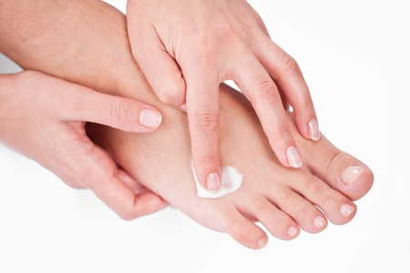 young woman applies cream on her foots. On a white background. photo