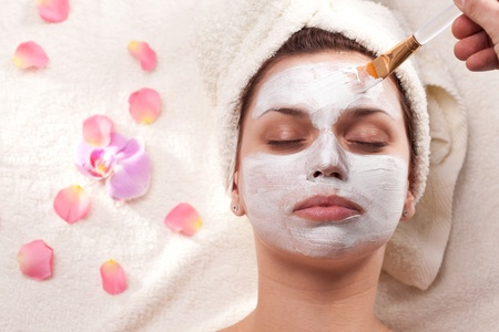 MÅ'oda kobieta uzyskiwanie bÅ'ocie maski w spa-salon. Zdjęcie Seryjne