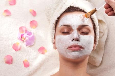 Young woman getting mud mask at spa-salon. photo