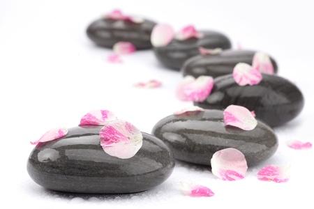 Spa pierres avec des pétales de rose sur fond blanc.