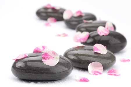 aromatherapy: Spa stones with rose petals on white background. Stock Photo