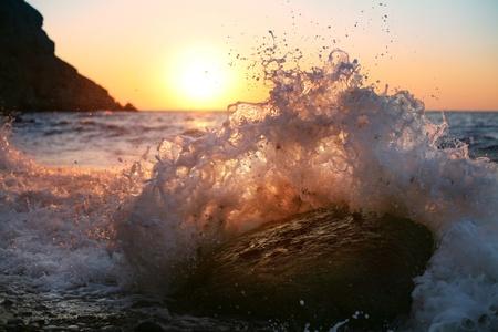 At sunrise, waves crash on the stone photo