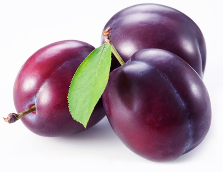 purple leaf plum: Three plums with leaves on white background.
