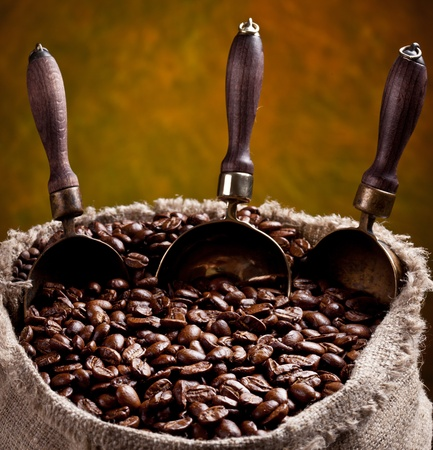beverage in bean: Sack of coffee beans and scoop. On a dark background.