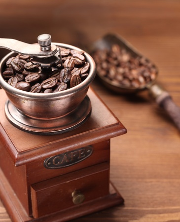 Roasted coffee beans are ground in a coffee grinder. Stock Photo