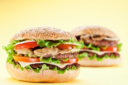 Two hamburgers on yellow background. Stock Photo - 9074247