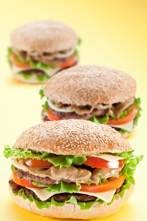 Three delicious hamburger on a yellow background Stock Photo - 9074252