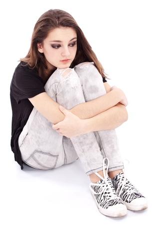 adolescentes estudiando: Adolescente de ni�a triste sienta trepadores armas sobre las piernas. Aislado en un fondo blanco.