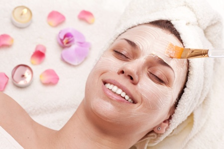 Applying of soothing mask, young woman getting spa procedures. photo
