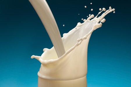 Splash of milk from the glass on a blue background Stock Photo - 9074176