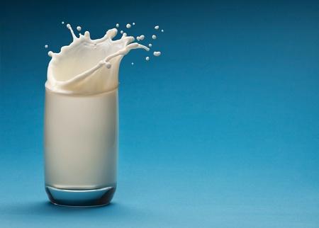 glass milk: Splash de lait de verre sur un fond bleu Banque d'images