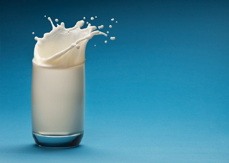 Splash of milk from the glass on a blue background photo