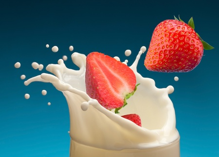 product mix: Splash of milk, caused by falling into a ripe strawberry. Isolated on a blue background. Stock Photo