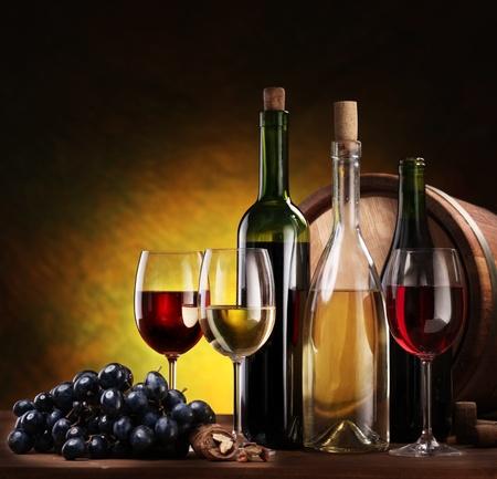 brown bottle: Still life with wine bottles, glasses and oak barrels.