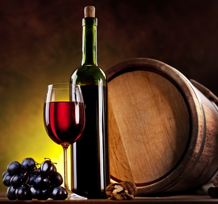 Still life with wine bottle, glass and oak barrels. photo
