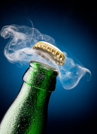 green glass bottle: Opening of beer cap with the gas output Stock Photo