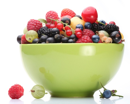 cherry varieties: Variety of berries in a green bowl on white background.