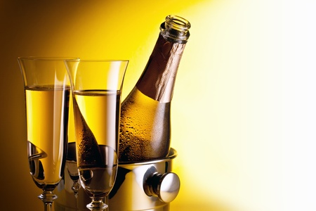 Champagne bottle in cooler and two champagne glasses. Isolated on a yellow. photo