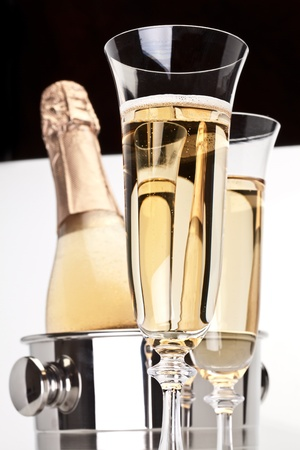 Champagne bottle in cooler and two champagne glasses. photo