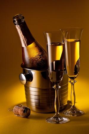 botella champagne: Botella de Champagne en el refrigerador y dos copas de champán. Aislados en un amarillo.