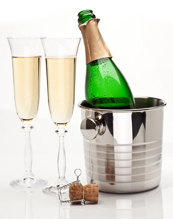 Champagne bottle in cooler and two champagne glasses. Isolated on a white. photo