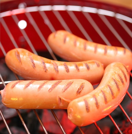 Hot sausages on barbecue photo
