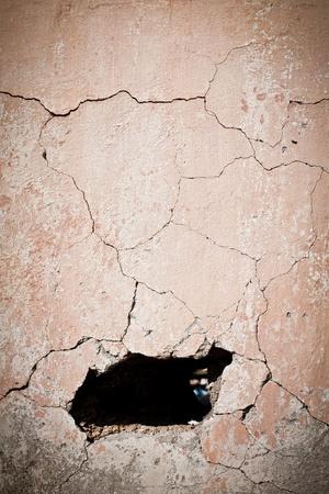 plaster wall: Agujero en el muro agrietado antiguo