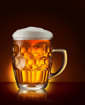 Glass of beer on the dark brown background photo