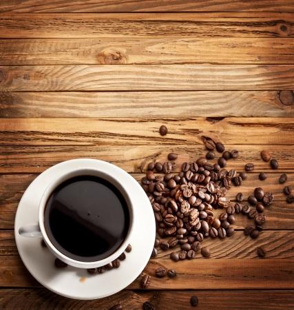 granos de cafe: Taza de caf�. Ver desde arriba en una superficie de madera. Foto de archivo