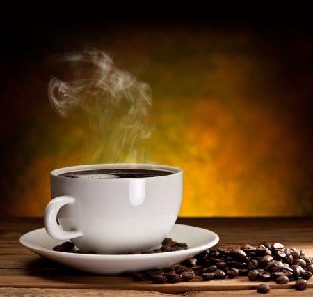 saucers: Cup of coffee with coffee beans on a beautiful brown background.