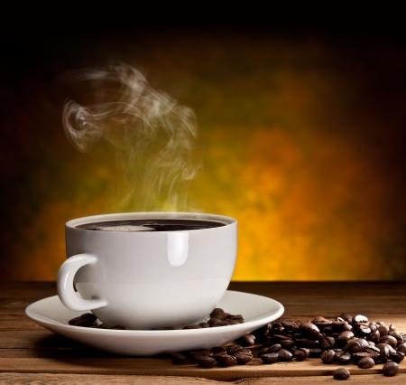 granos de cafe: Taza de caf� con granos de caf� en un hermoso fondo marr�n.