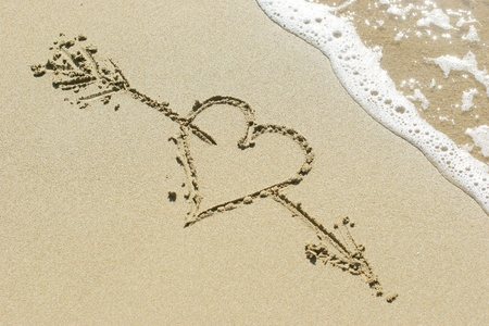 Heart pierced by Cupids arrow drawn in the sand photo
