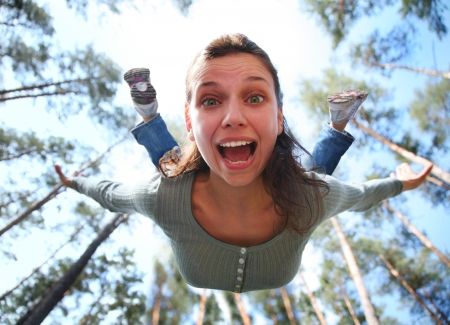 par: Woman falls from above the pine forest directly at you.