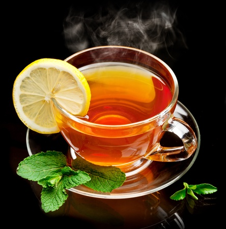 pekoe: Cup tea with mint and lemon isolated on a black background.