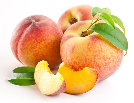 Ripe peach fruit with leaves and slises on white background. Stock Photo