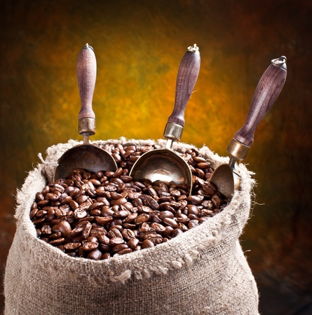 wooden scoop: Sack of coffee beans and scoop. On a dark background.