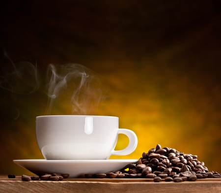 Cup of coffee with coffee beans on a beautiful brown background. photo
