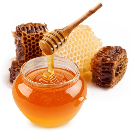 honey comb: Pot of honey and wooden stick are on a table.