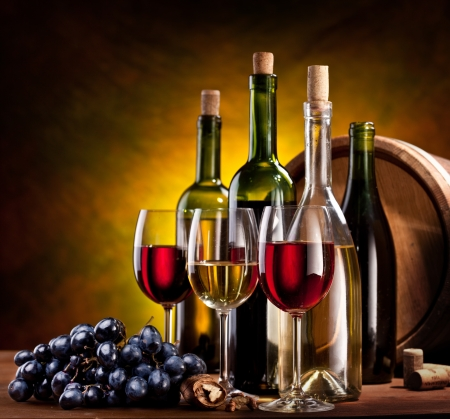 Still life with wine bottles, glasses and oak barrels.  photo